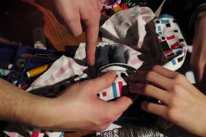 15 Hubert Glasner, Robert Kuzniewski, Daniel Kuzniewski probieren Stoffe für die Bekleidung von Puppen aus Nah